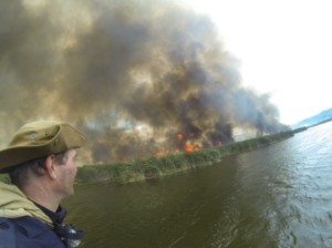 The Otter Bush Camp burning as seen from the Rondevlei water.